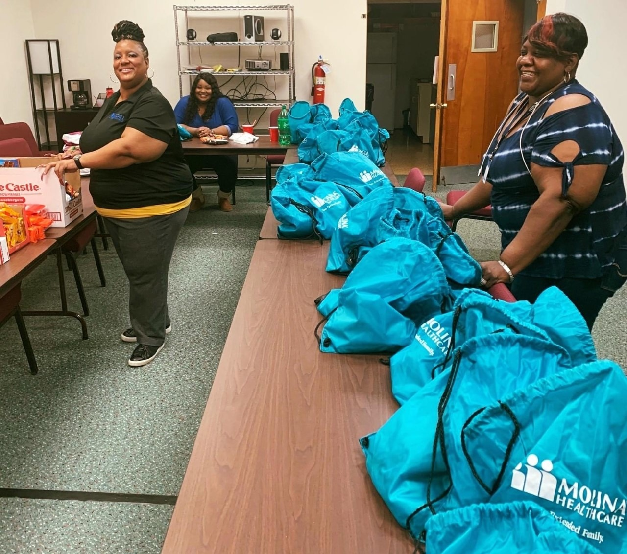 Three woman of color stand around a table of care packages smiling