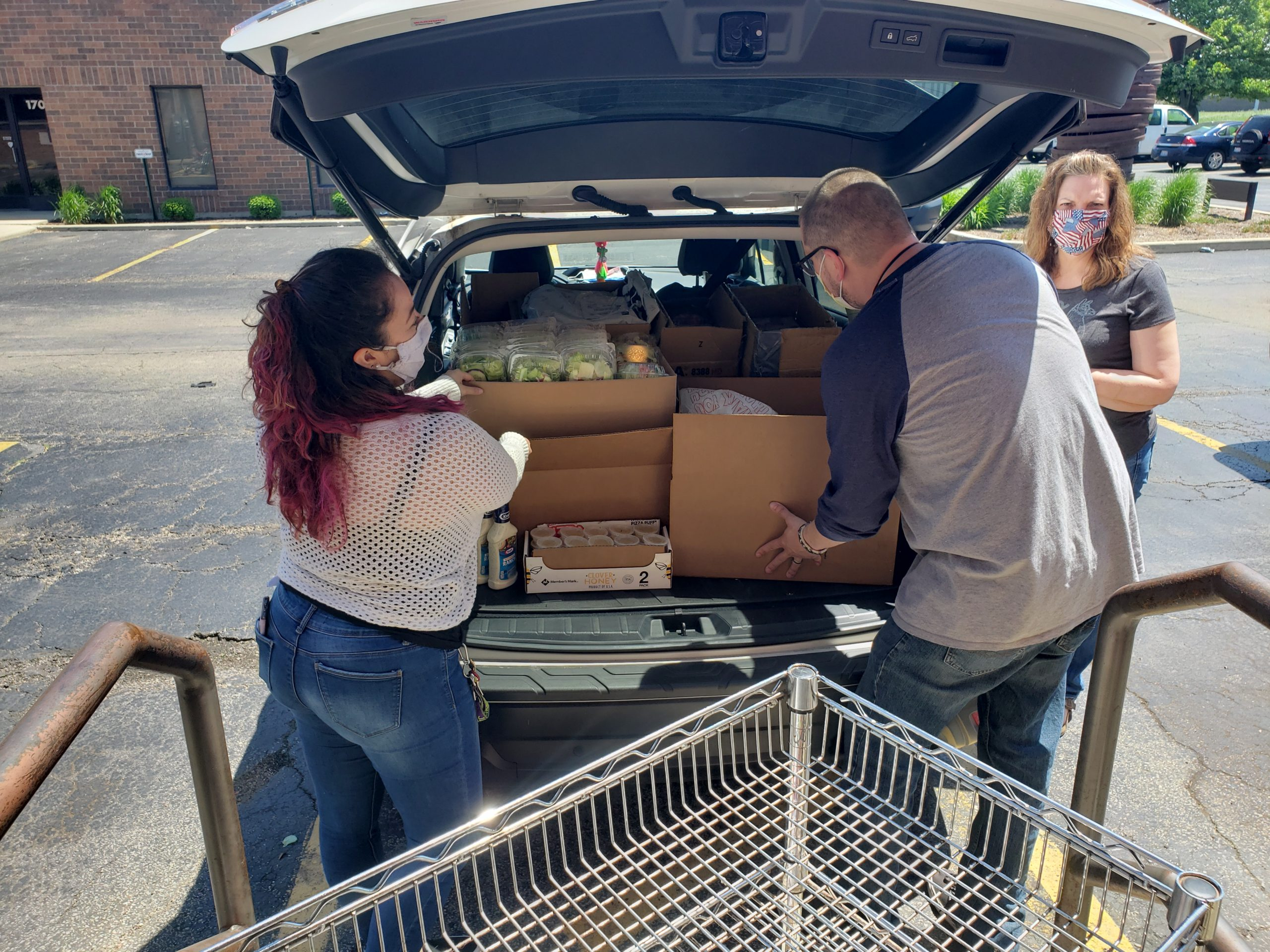 Volunteers loading truck of car with groceries