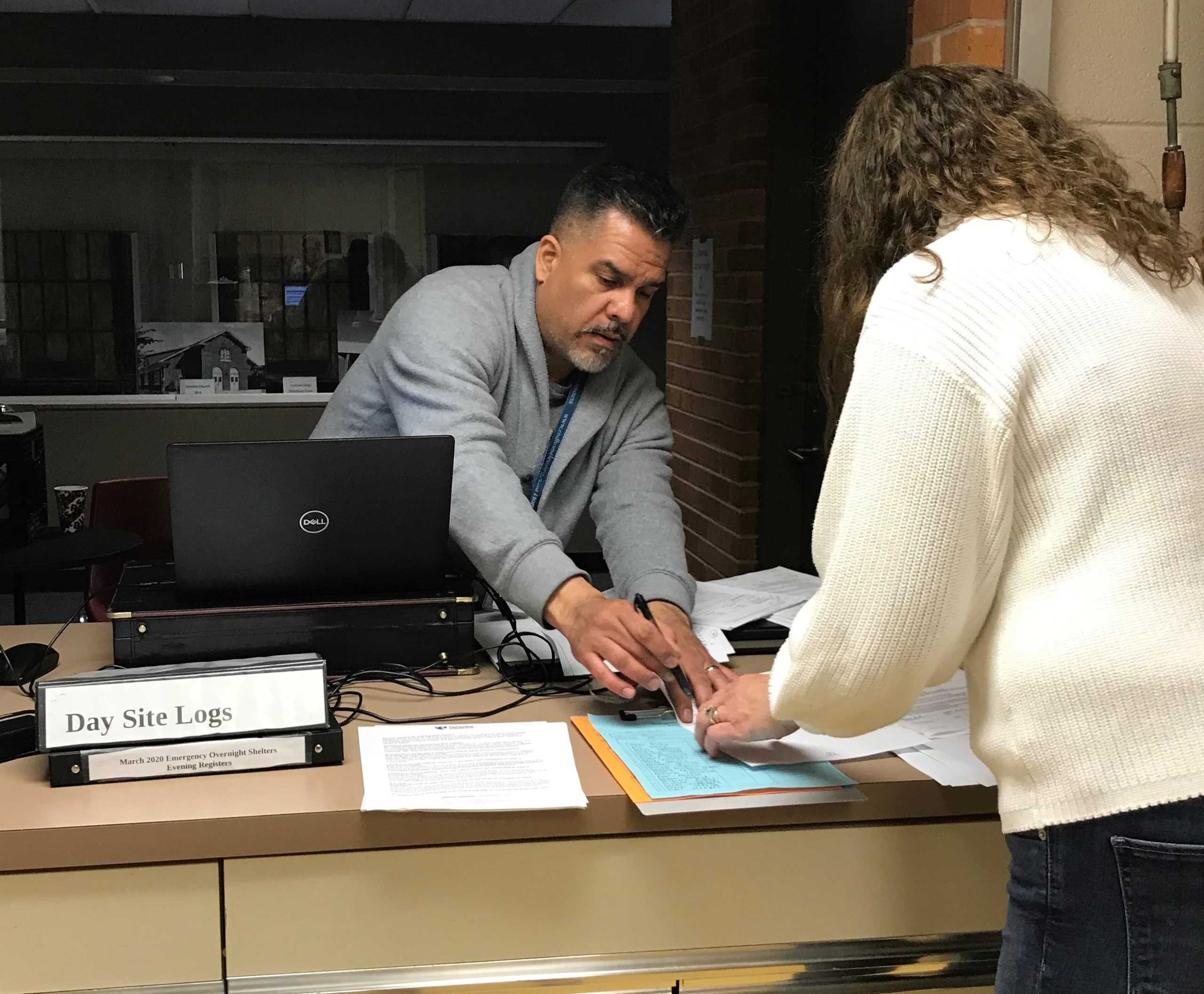 Man leaning over to sign paper work for a woman while also on the phone