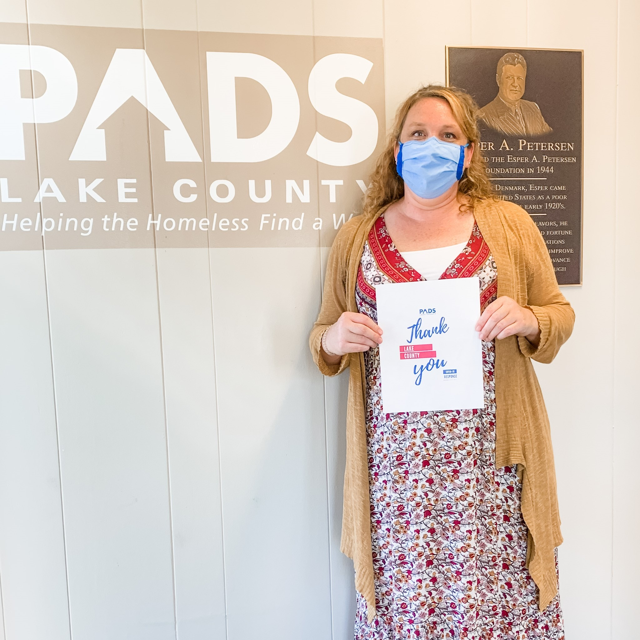 Volunteers in mask stands next to PADS Lake County sign