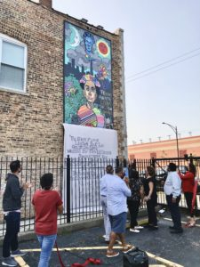 group of people gathering and looking up at a mural