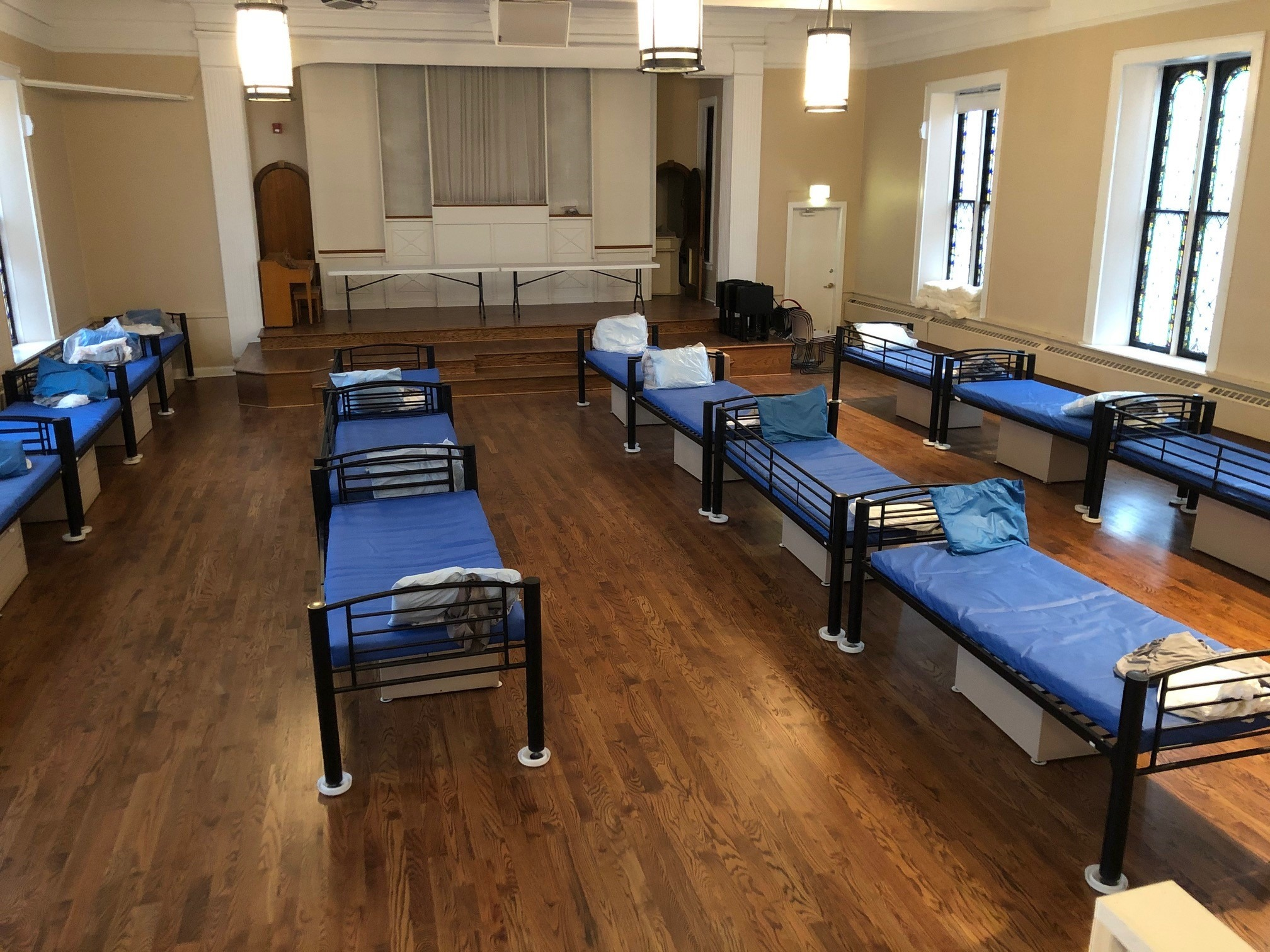 Room full of evenly spaced blue cots